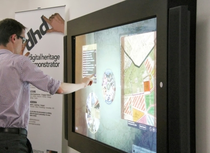 A man uses a wall-mounted touch screen to explore some map data
