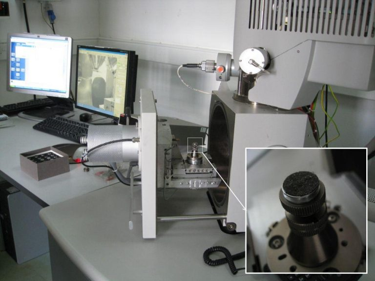 Figure 1. A sample of repository dust on a sticky carbon tab (inset) awaiting SEM-EDX analysis.