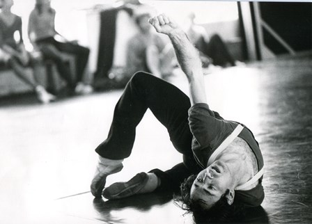 An image of a male dancer in a complex semi-supine pose