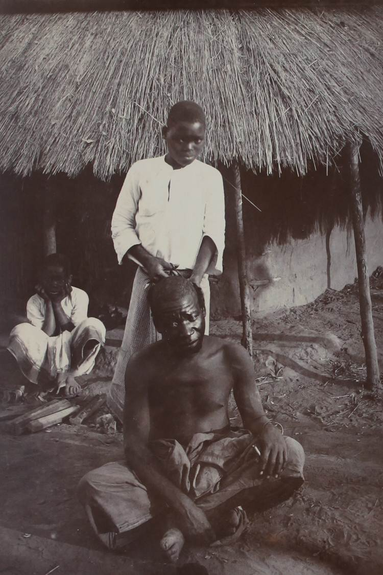 Photograph of a native barber (hair cutting) Blantyre, British Central Africa. Catalogue reference: COPY 1/435/102.