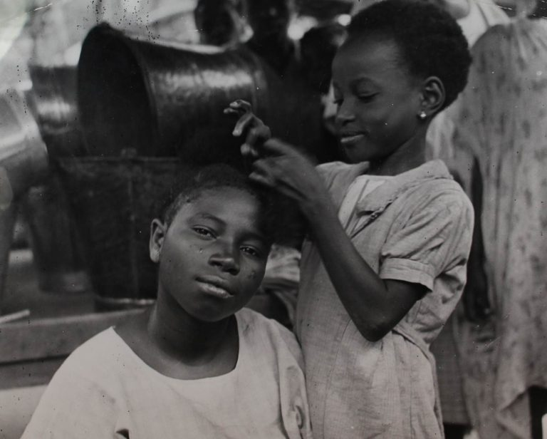 Nigeria. Girl aged eight, dressing her mother's hair in the 'King' or 'Chuku' hairdress. Catalogue reference: INF 10/ 254/ 13.