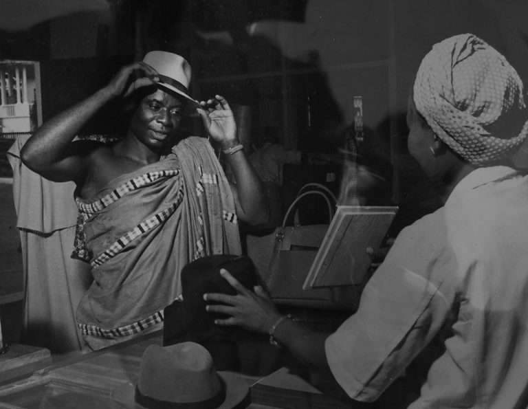 Gold Coast. 'Mr Akwasi Kuh buys a hat at the central store of the Kumasi Co-op. He is secretary of his village co-operative society which handles farmers' cocoa as well as supplying retail requirements (catalogue reference: INF 10/117/28)