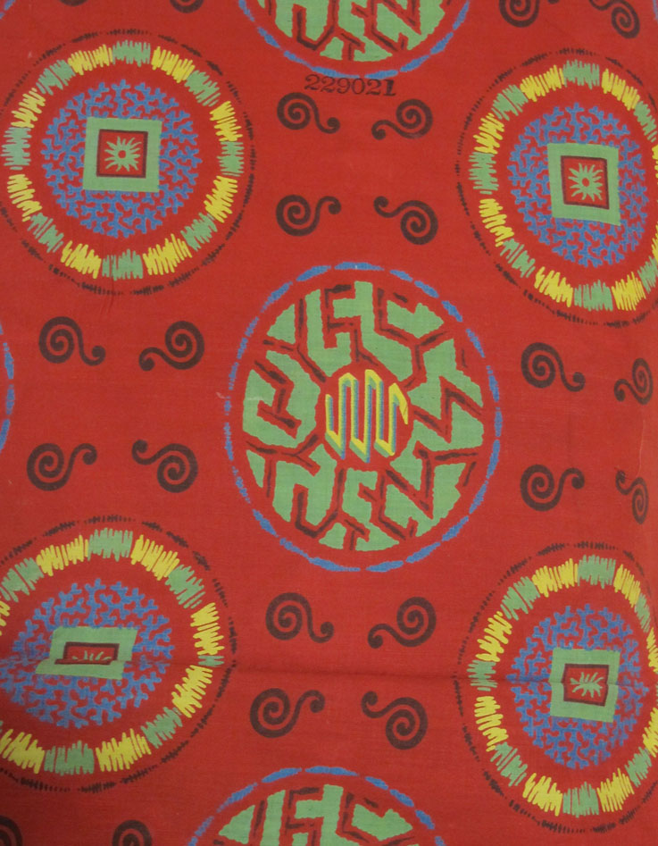 Image of red textile sample with a green, yellow and blue circular pattern