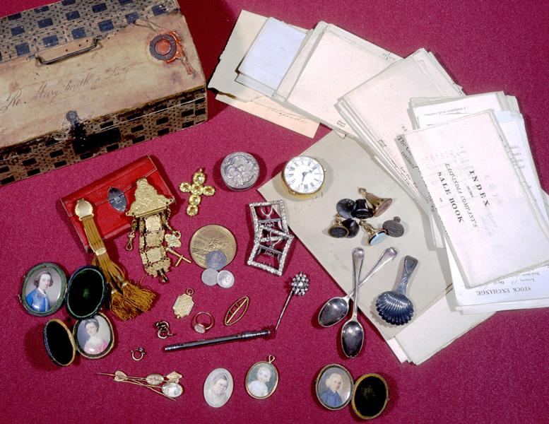 An image of the contents of the jewellery box of Mary Smith, including silver spoons and brooches