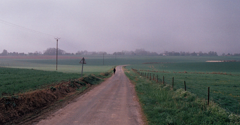 Image of Sarah Kogan standing in a road surrounded by fields in Gommecourt, 2014