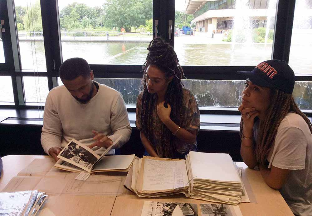 Image of Knowlton, Amandla and Lenora Crichlow looking at records relating to their father's experience of the Mangrove Nine trials