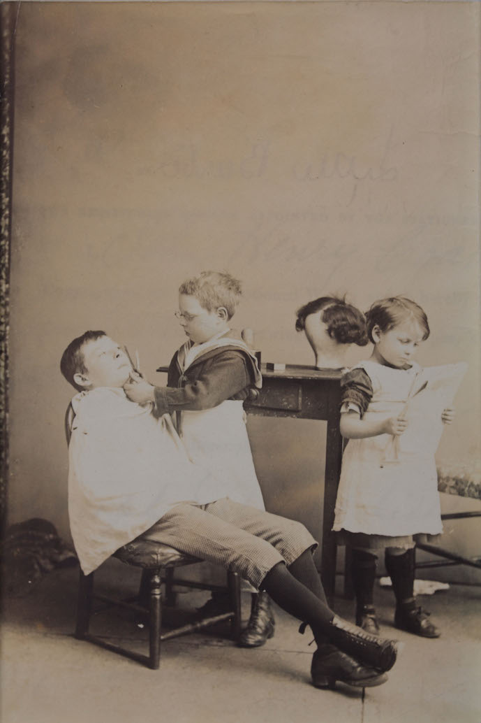 Image of a photograph of three children posing as if they are in a barber's shop