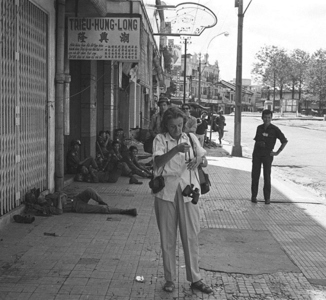 Black and white photograph of Clare Hollingworth standing in the middle of a street, Place Saigon, looking at her binoculars
