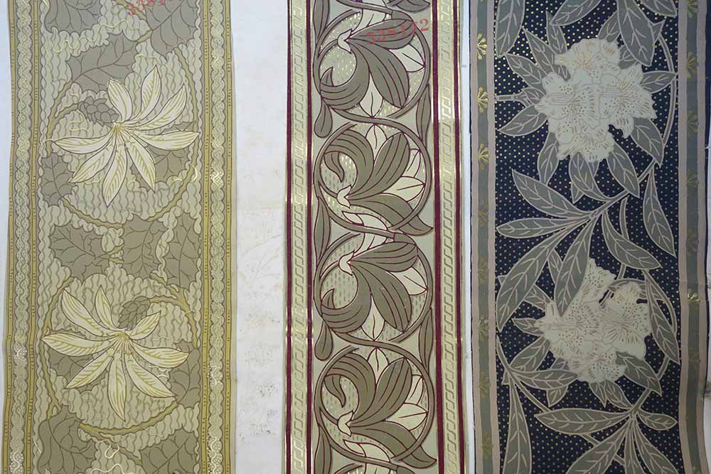 A set of three different wallpaper borders, each with a floral design. The central design includes maroon, dark green, pale green and gold-coloured pigments and was registered in 1879 by William Cooke, Leeds.