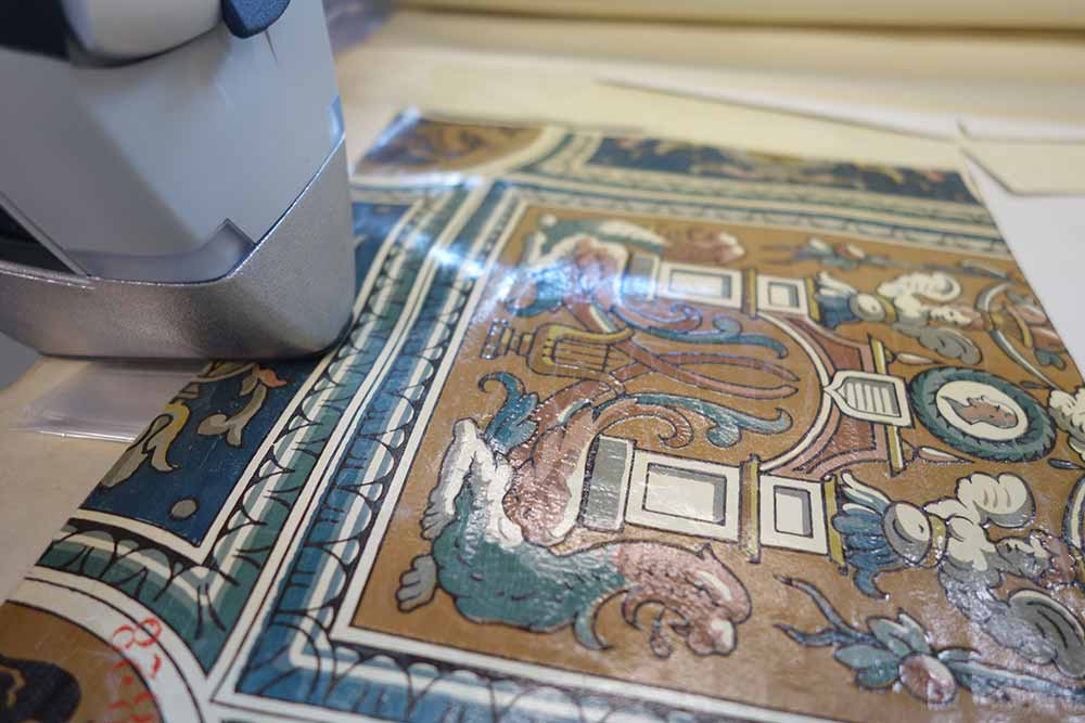 Detail of XRF analysis being undertaken with the front of the analyser in contact with a highly detaile wallpaper sample. The surface of the wallpaper is shiny and the design includes architectural features in predominantly blue/green, cream, and brown colours.