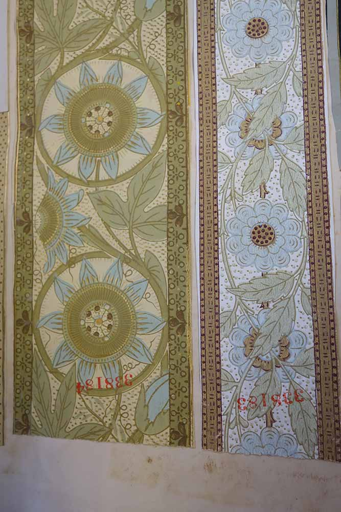 Two samples of wallpaper borders featuring flowers and vines in blue, green, and cream shades with gold details. The design on the right was registered by William Cooke, Leeds, in 1879.