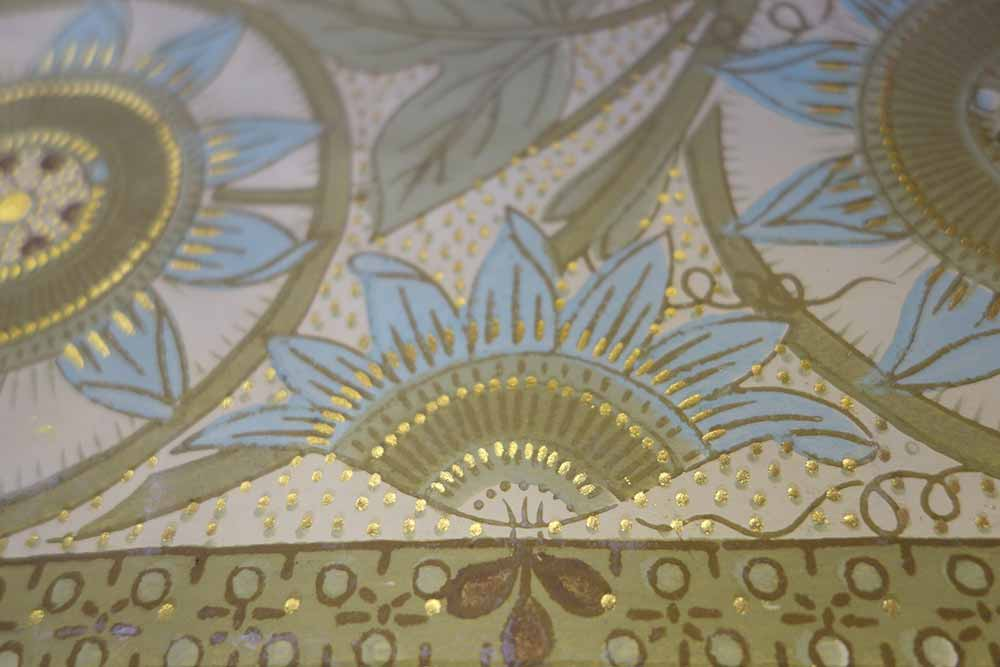 Detail of the pattern of wall-hanging design, showing a flower with blue petals embellished with gold