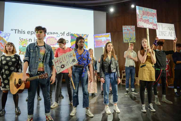 A group of students wearing colourful clothing and holding up protest signs