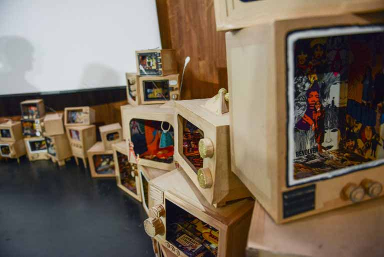 Cardboard boxes with painted scenes inside