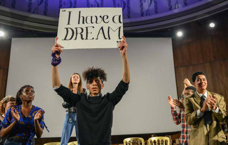 Student holds up a placard with 'I have a dream' written on it