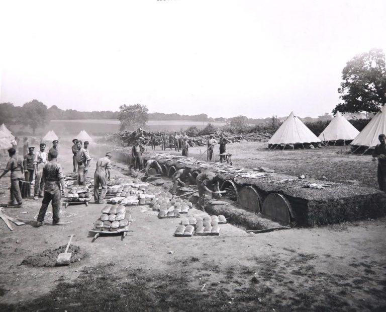 Black and white photograph of a field bakery: there are neat piles of bread, and men crouching in front of the ovens