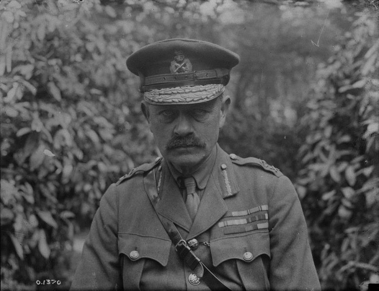 Black-and-white photo of a uniformed man with a moustache, wearing an officer's cap and a Sam Browne belt. His tunic is festooned with medals and military decorations, and he is staring directly and impassively into the camera.