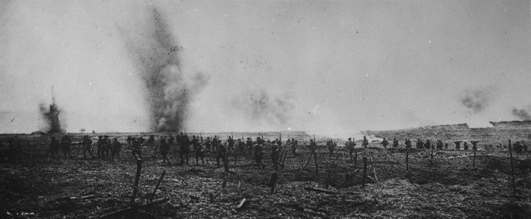 Black-and-white photo of soldiers advancing across a field, with shells exploding just in front of the advancing column.