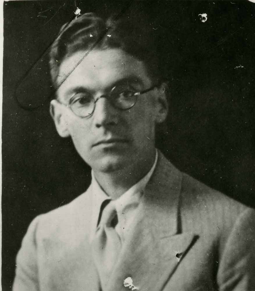 Black and white photograph of Desmond Costello, wearing round glasses