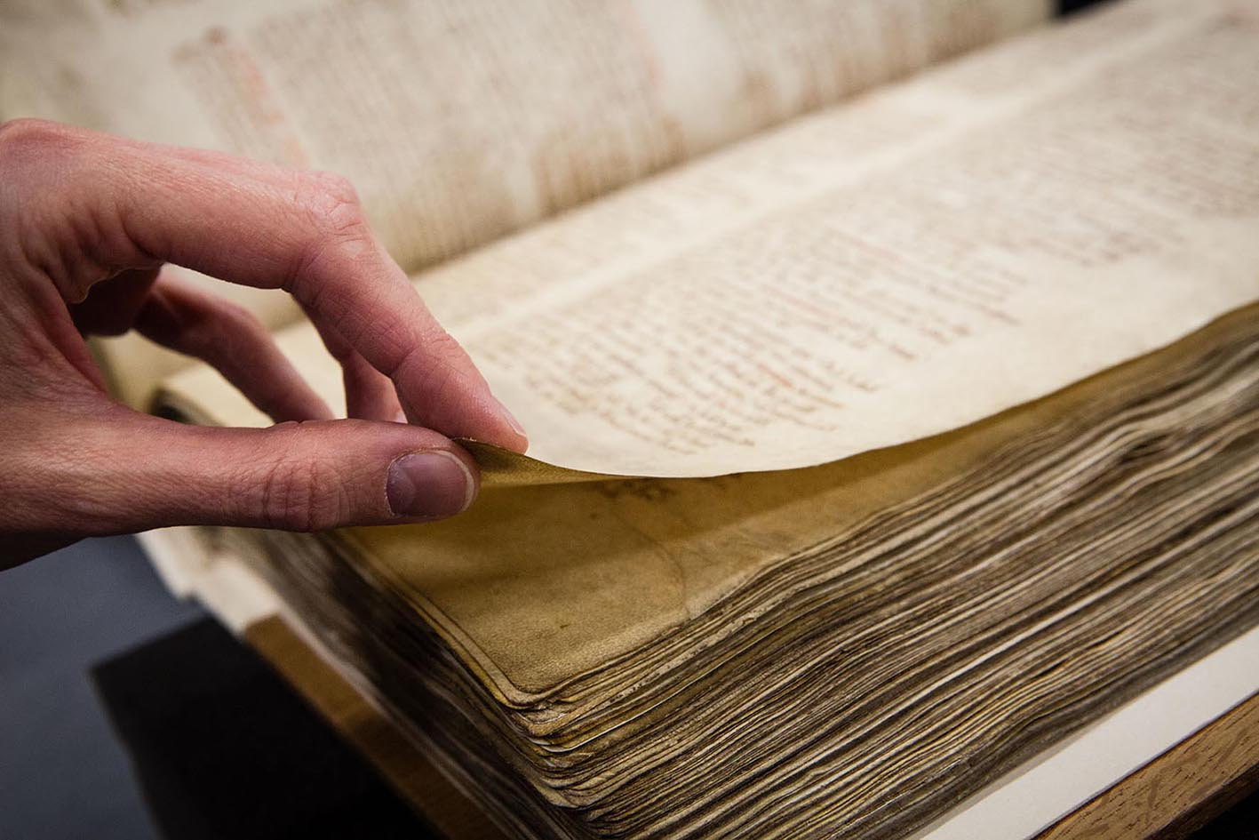 Colour photograph of someone turning the pages of Domesday Book