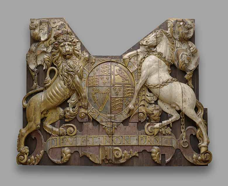 Image of a wood carving of a lion and unicorn holding a shield that bears the royal coat of arms
