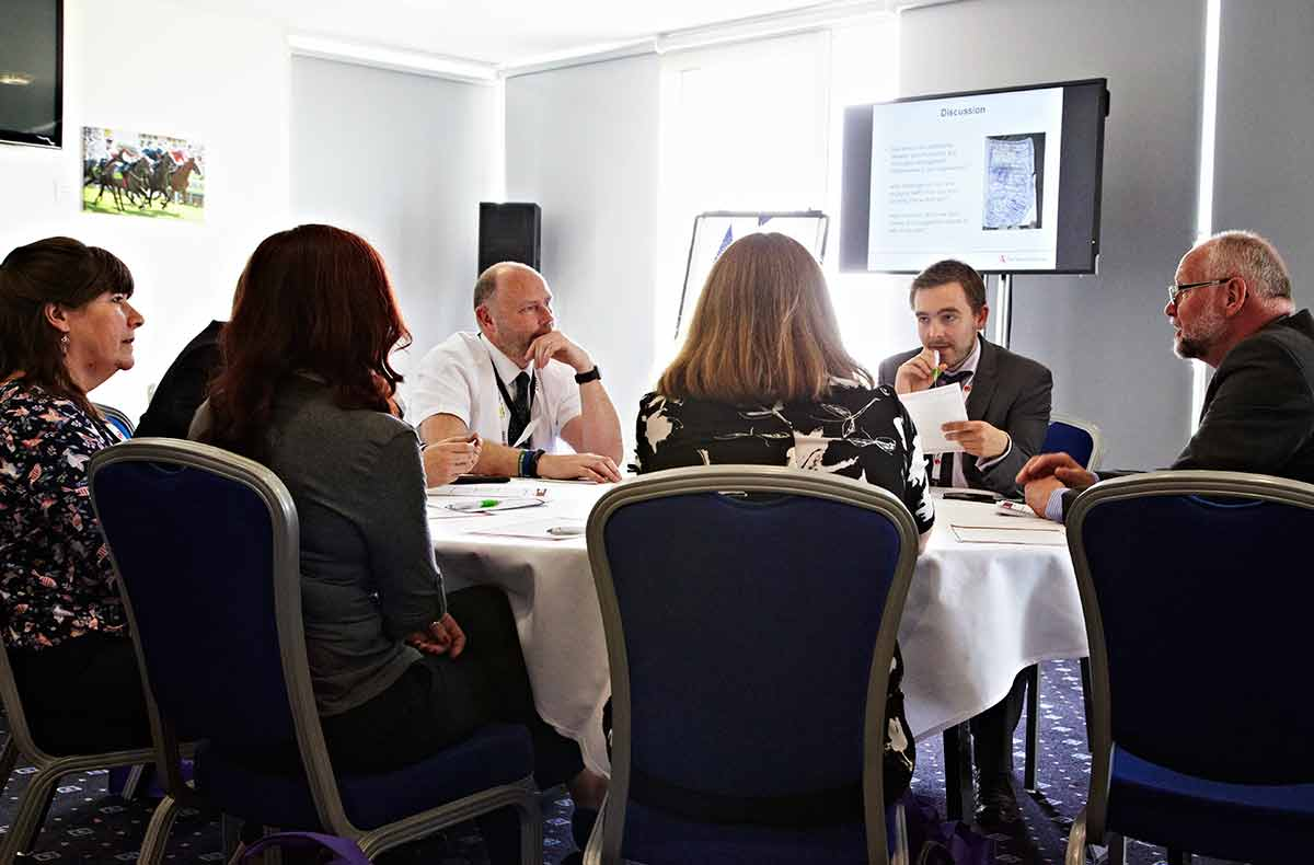 A group of people in discussion sit at a round table