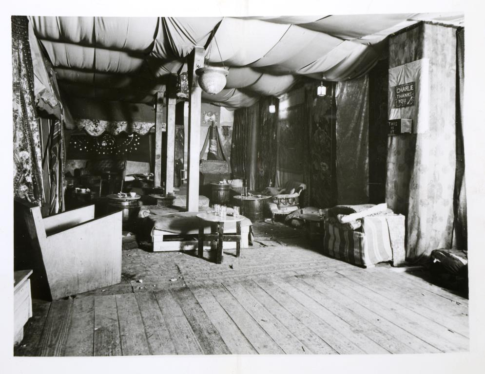 Black and white photograph of the interior of The Caravan Club; the room have fabric draped across the ceiling, and low chairs and tables