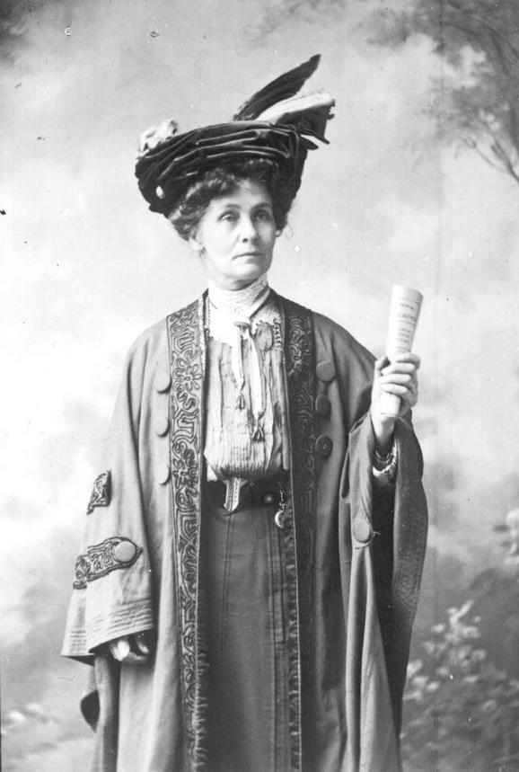 Photograph of Emmeline Pankhurst leader of the Women's Social and Political Union, London three quarter length hand upraised holding paper wearing hat and cloak