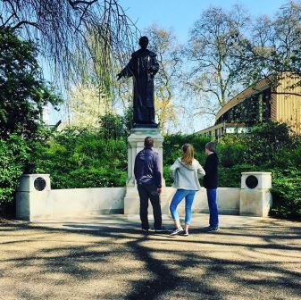 Colour photograph of three people looking at the Emmeline Pankhurst memorial at Victoria Tower Gardens