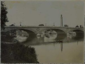Photograph of Kew Bridge, recently opened by King Edward VII; taken from Surrey side, showing boat in foreground and one in distance, 1903