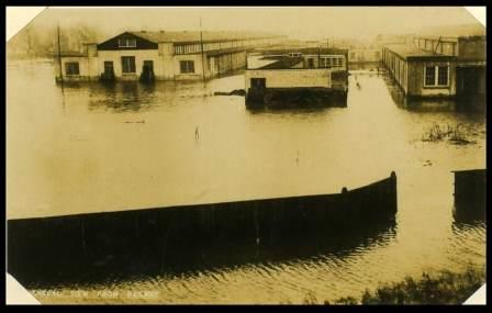 This image, taken from the railway line, shows the extent of flooding to the site in the 1920s before the raising of the river embankment