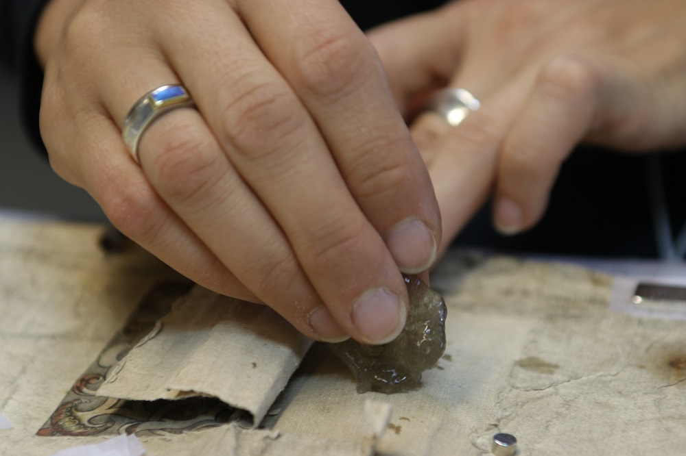 A photo showing Sonja cleaning an 18th century hand painted map using gels