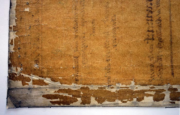 After treatment – close up of flattened linen cloth edge and re-adhered transparent paper fragments