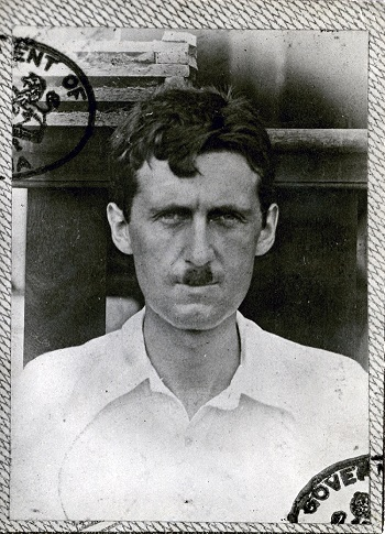This photograph shows Eric Blair (George Orwell) in 1936. He is wearing an open necked shirt and has slightly tousled hair and a small moustache