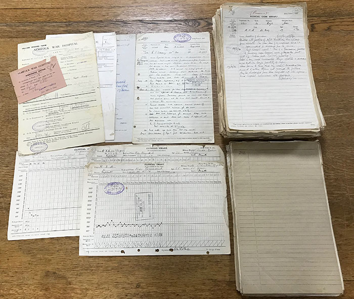 A selection of documents from the MH 106 series in numerous stacks on a table.