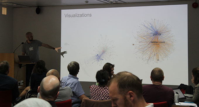 Giovanni Colavizza, Senior Researcher at The Alan Turing Institute, stands in front of a screen and presents his group's work on visualising data from The National Archives' Web Archive to an audience seated at desks.
