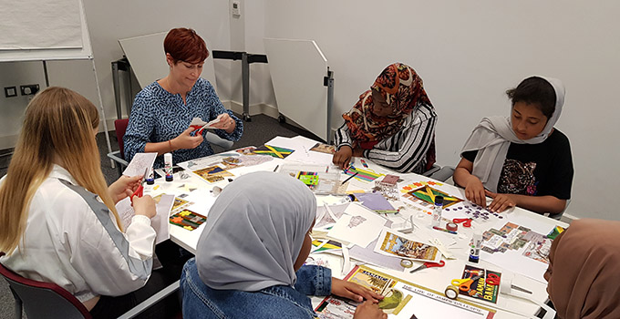 Students from Fitzalan High School taking part in a group working session at Glamorgan Archives. The participants are seated around a table making a collage.
