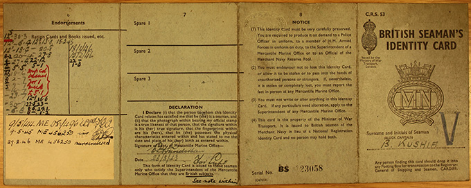 In two parts, this is the British seaman's identity card for Kushi Bag. It includes his photograph, fingerprints and personal information.