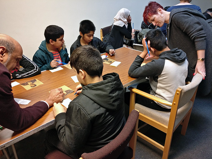 Young people sitting around a table, taking part in an education workshop looking at copies of records from The National Archives.