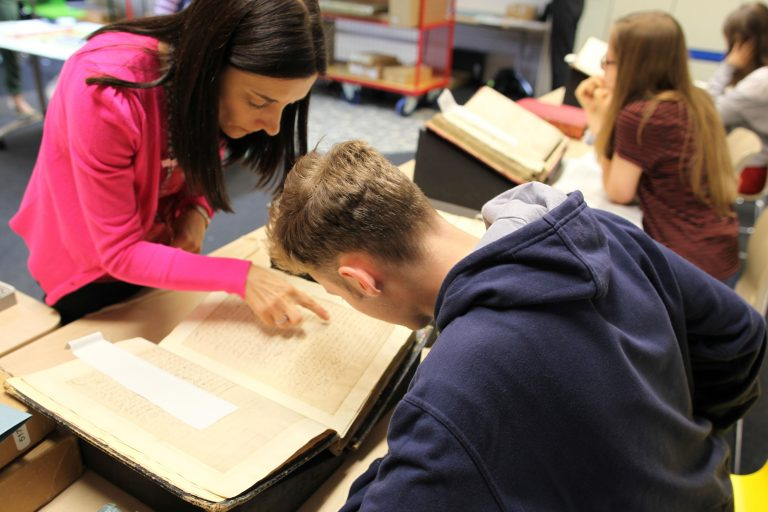 A teacher helps a student working with a Tudor document