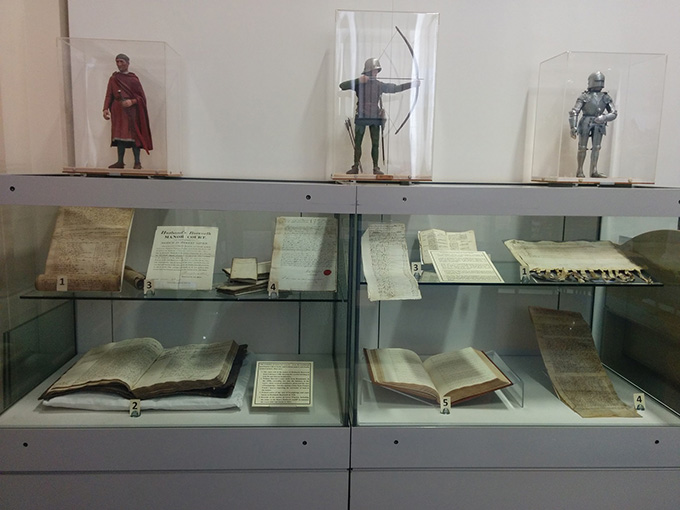 A display case for the touring exhibition featuring a few examples of documents from the manorial register in a glass exhibition case.