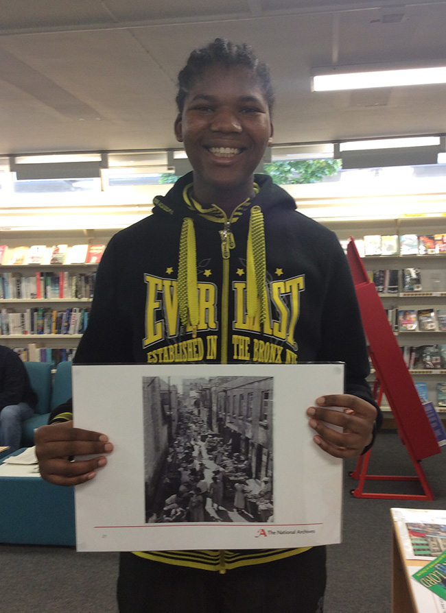 Rephael holding up a photographic image of INF 10/39/3 – recalling market places in London and Jamaica.
