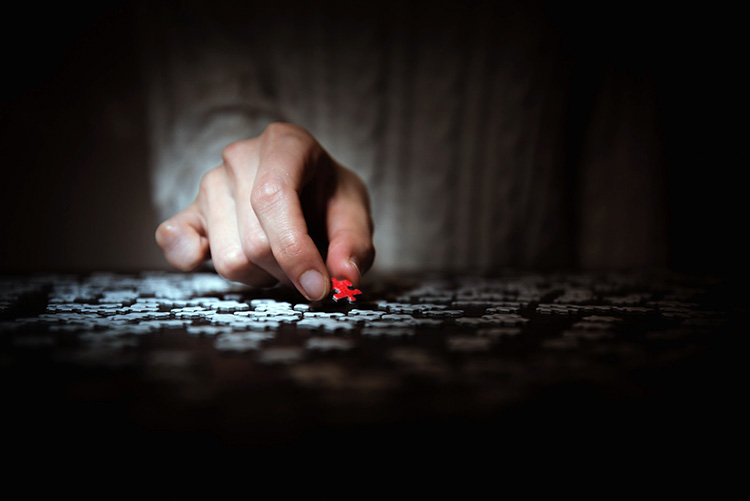 Artistic photograph of a hand placing a piece in a jigsaw puzzle.