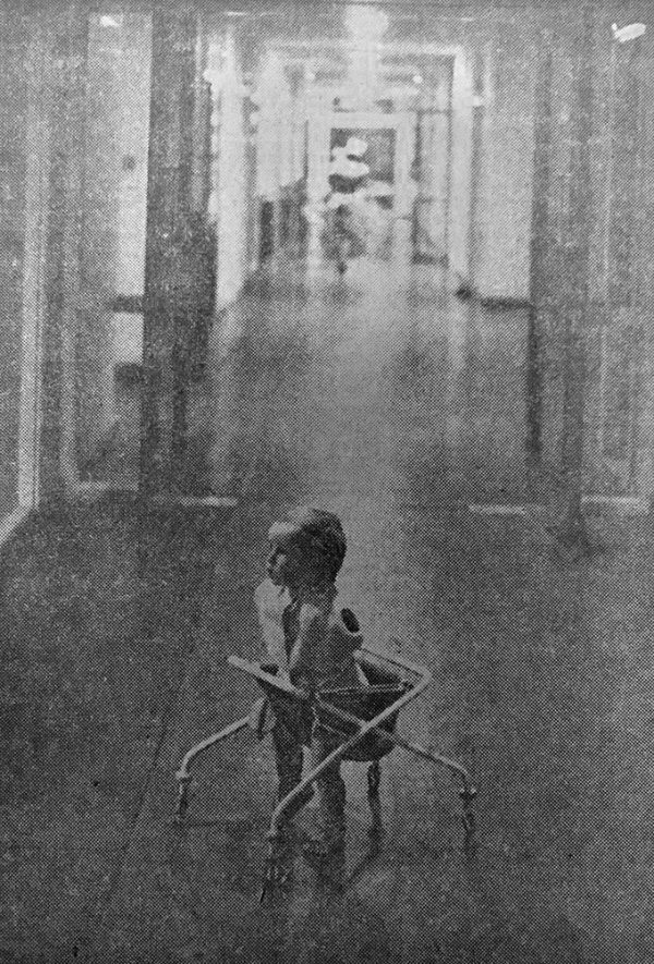 Black and white image of Philippa, the first baby to be fitted with powered arms. The baby is pictured in a dress, supported by equipment, and she is in the foreground of a hospital corridor. The image was found as part of a newspaper clipping in The National Archives collections.