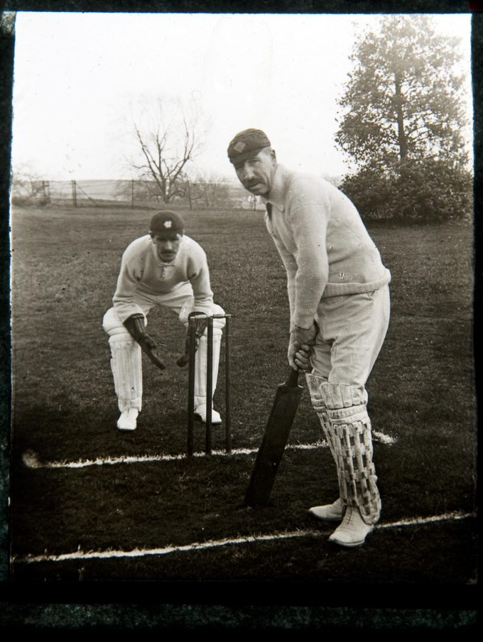 Black and white photograph showing cricketer miner Tom Oates at the wicket in 1912. A wicket keeper stands a yard away behind the stumps.