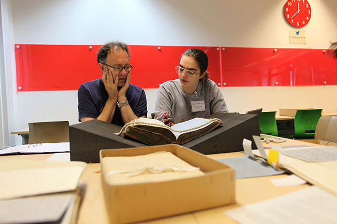 Nigel and Roberts researching a bound volume document on a set of document wedges to support the spine.