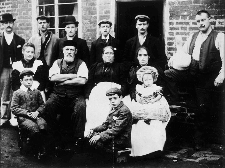 Black and white photograph of thirteen members of the Lowe family during the Victorian era.