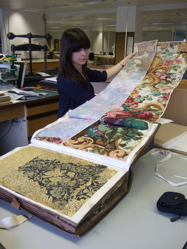 Conservator looking at a BT design register.