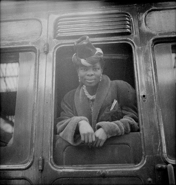 Princess Omo-Oba Adenrele Ademola leaning out of train window, smartly dressed, in 1944/45.
