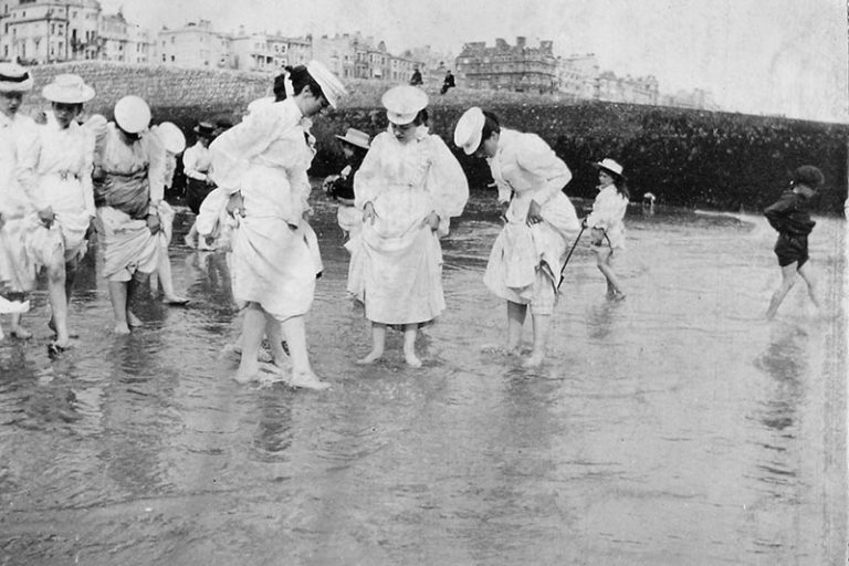 An old black and white photograph of a group of fully-clothed ladies paddling.